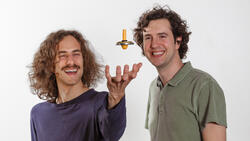 Cosimo Rusconi (l.) and Oriol Romero-Isart (r.) play with a levitron to illustrate their work on nano magnets.