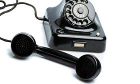 The picture shows an old telephone with dial disc