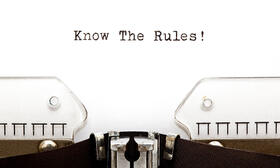 The picture shows a sheet of paper clamped in a typewriter with Know The Rules on it.